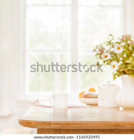 Home wooden kitchen table top with focus in front and blurred background showing breakfast tablewear, windowframe and a vase filled with garden flowers. Space for text.