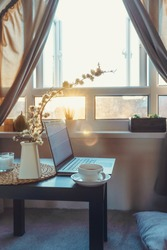 Home work place with laptop, cup of hot drink and blooming brunch in vase on coffee table near window on sunset or sunrise. Freelance, working from home, online learning, studying, home office concept