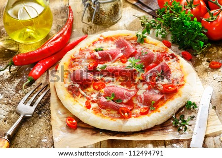 Homebaked pepperoni pizza with a delicious topping of salami, chilli peppers, cheese and tomato on a thick golden crust