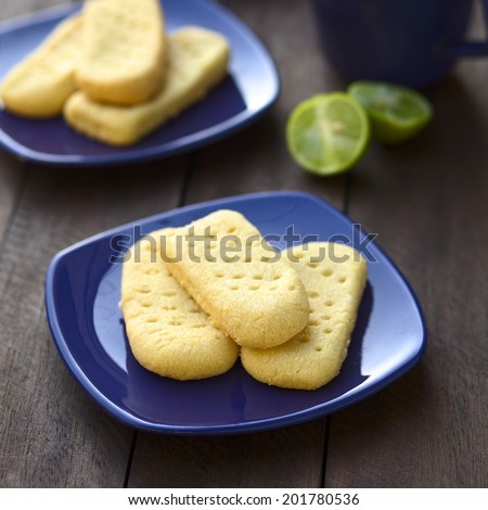 Homebaked shortbread biscuits on small plates with cup of tea in the back (Selective Focus, Focus on the front of the upper shortbread)