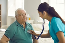 Homecare nursing service and elderly people cardiology healthcare. Close up of young hispanic female doctor nurse check mature caucasian man patient heartbeat using stethoscope during visit