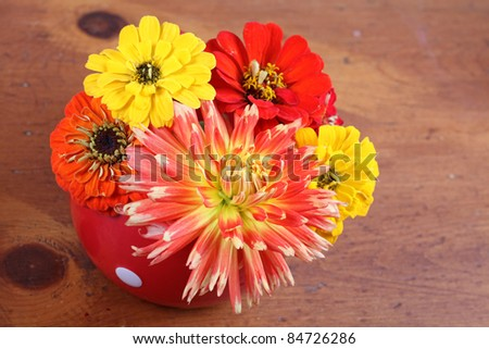 Homegrown fall garden flowers in a bright red dish, on a wooden table.