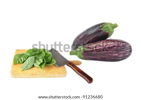 Homegrown Garden Farm Fresh Delicious Mediterranean Striped Eggplant and Basil Leaves on Wood Cutting Board with Butcher Knife isolated on white background