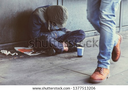 Homeless adult man sitting on the street in the shadow of the building and begging for help and money. Problems of big modern cities. Indifference of people. Social issues. Foto d'archivio ©