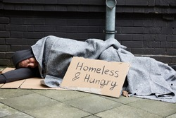 Homeless And Hungry Man Sleeping On Street With Begging Signboard