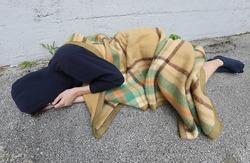 homeless as he sleeps on the floor under a filthy blanket