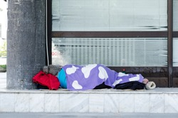 Homeless barefooted woman sleep on the urban street in the city on the sidewalk near the building