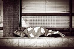 Homeless barefooted woman sleep on the urban street in the city sidewalk near building