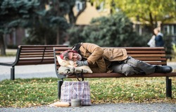 Homeless beggar man with a bag lying on bench outdoors in city, sleeping.
