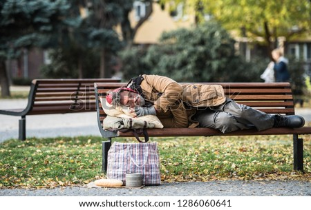 Homeless beggar man with a bag lying on bench outdoors in city, sleeping. Foto stock ©