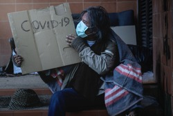 Homeless begging man with a medical mask sits on the steps holding a brown cardboard, The word