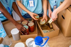 Homeless care. Charity team of volunteers putting food and drinks into paper box. Volunteers Collecting Food Donations In Warehouse. Volunteers with donation box with foodstuffs on wooden background