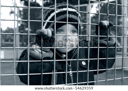 homeless child looking through fence, bored boy