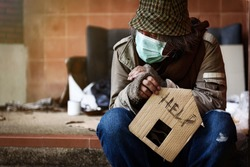 Homeless holding a cardboard house living on the streets in the city. Get help with housing problems concept. unfocused people as background.