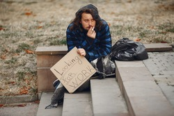 Homeless in a city. Man asking for food. Man with a tablet