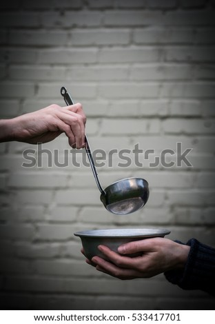 Homeless. In the hands of one man metal plate. In the hand of another person ladle.  #533417701