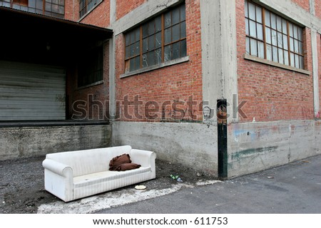 homeless living room - couch out in an old industrial alley