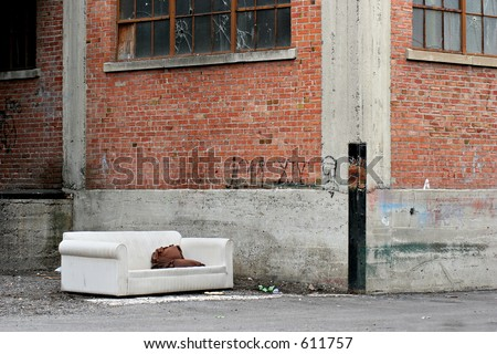 homeless living room in the city, a couch in an old industrial alley