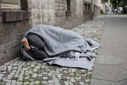 Homeless Man Covered With Blanket Sleeping On Street In City