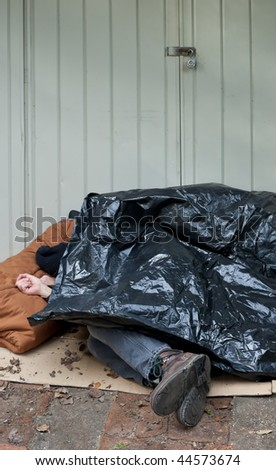 Homeless man curled up on the street under a plastic tarp.