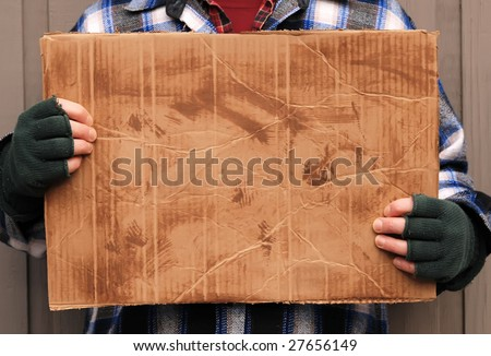 homeless man holding up blank cardboard sign - stock photo