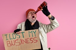 homeless man in dirty wear lost his business job that is why now he has no money and home, suffering from alcohol addiction, isolated pink background