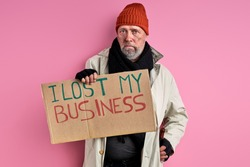 homeless man in dirty wear lost his business job that is why now he has no money and home, isolated pink background