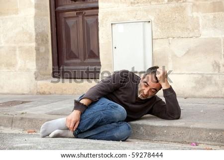 homeless man lying in city street near house door