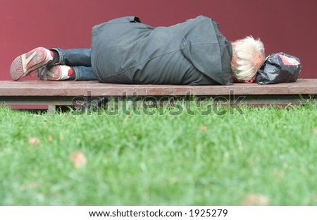 Homeless man lying on the bench. - stock photo