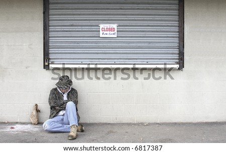 Homeless man outside of a closed business that has gone bankrupt