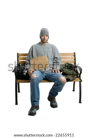 Homeless man sits on a bench, his possessions contained in his backpack next to him. Dressed for cooler weather w/ a stocking cap and fleece shirt. He has a cardboard sign on his lap, which is blank.