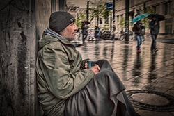 Homeless man sits on a wall of a house in the rain