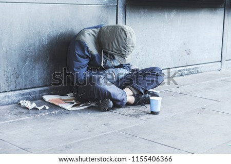 Homeless man sitting on the street in the shadow of the building and begging for help and money. Problems of big modern cities.