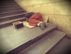 Homeless man sleep on the stairs, in the subway blurred. Social documentary.