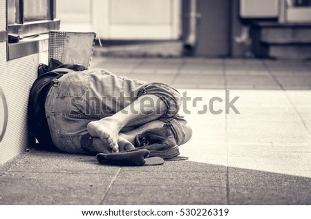 Stock Photo Homeless man sleeps on the street in the shadow of the building.