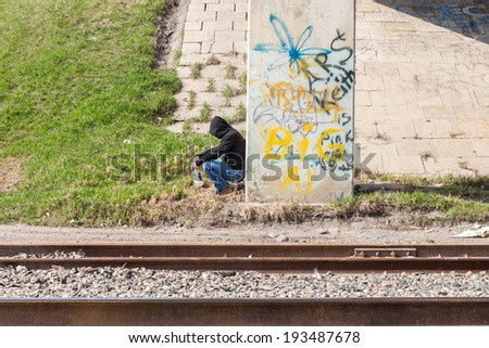 homeless man with a whiskey bottle sitting against a stone wall with graffiti written on it wearing a black hoodie and jeans and sunglasses. stock photo