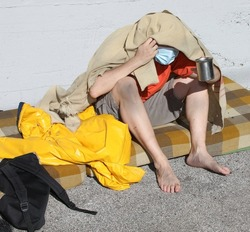 homeless man with filthy and dirty feet asking for charity covered by a blanket and surgical mask for virus protection