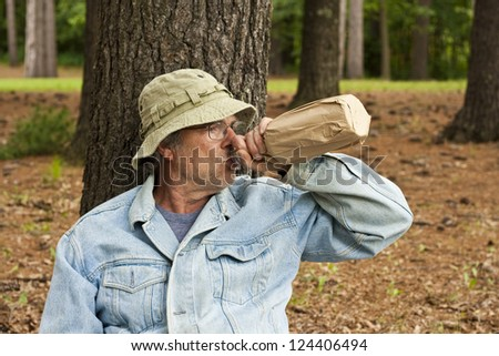 homeless man with his bottle in a park