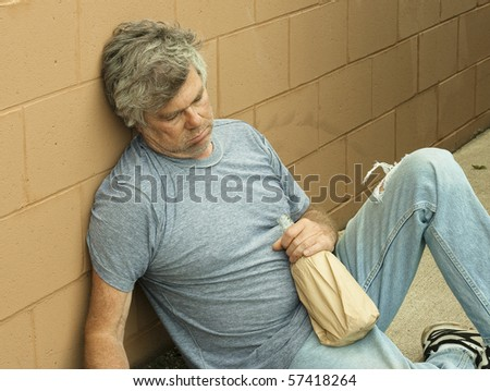 homeless man with his bottle passed out in an alley