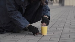 Homeless person taking coins from pavement on city street.