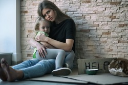 Homeless poor woman and her little daughter sitting near brick wall and asking for help