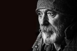 Homeless senior man portrait on black background