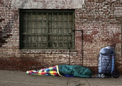 Homeless Soul Sleeping on the Streets in a Sleeping Bag Outdoors