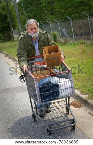 Homeless Vietnam veteran pushes a shopping cart containing his possessions down the side of the street.