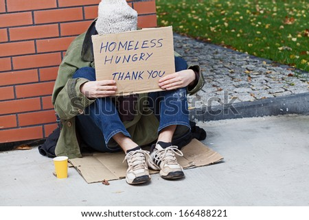 Homeless with cardboard on his neck drinking hot tea