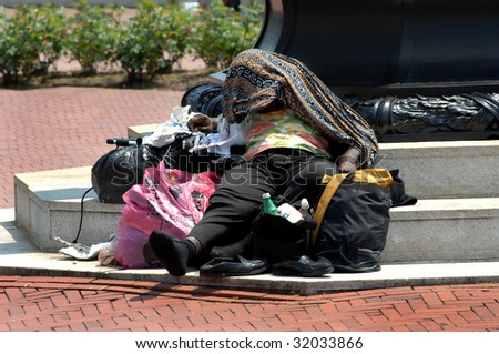Homeless woman covers her head for relief from the suns heat while laying at the foot of a monument in downtown Washington DC.