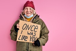 homeless woman without home hold cardboard with iscription ONCE I WAS LIKE YOU, social issues concept. female needs shelter and food, but nevertheless she smiles