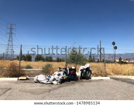 Homelessness person's belongings at the edge of a vacant lot and a parking lot #1478985134