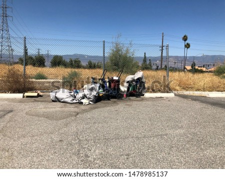 Homelessness person's belongings at the edge of a vacant lot and a parking lot #1478985137