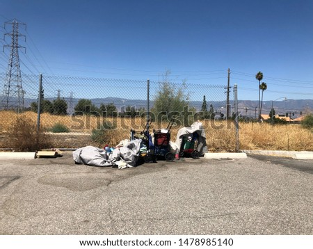 Homelessness person's belongings at the edge of a vacant lot and a parking lot #1478985140